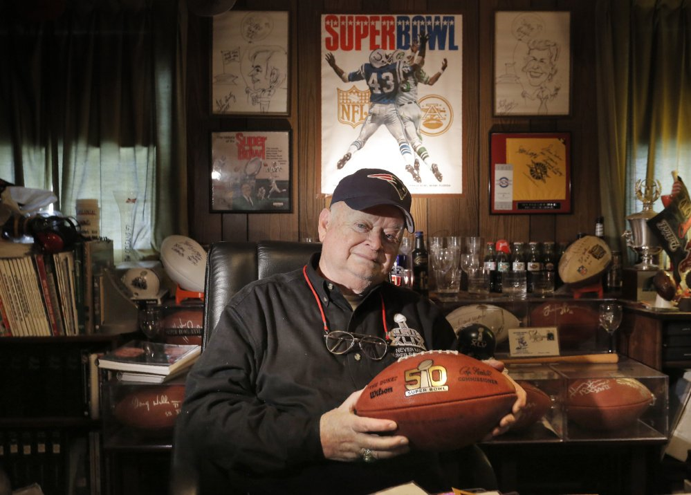 Patriots fan Don Crisman holds a Super Bowl 50 football at his Kennebunk home, which features a room dedicated to sports memorabilia, including items from his 50 trips to the Super Bowl.
